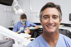 Portrait Of Dental Nurse With Dentist Examining Patient In Background Royalty Free Stock Images