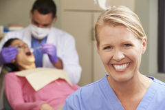 Portrait Of Dentist And Dental Nurse In Surgery Stock Image