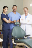 Portrait Of Dentist And Dental Nurses In Surgery Stock Image