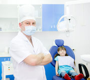 Portrait dentist with patient in the background. Stock Photography