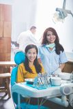 Dentist smiling with female patient in dental clinic royalty free stock photography