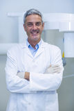 Portrait of dentist standing with arms crossed Stock Photos