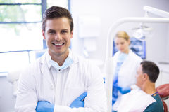 Portrait of dentist standing with arms crossed. While his colleague examining patient in background Stock Photography