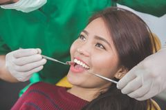 Dentist taking care of female patient Stock Images