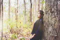 Portrait of depress and hopeless young woman calm herself. In forest at countrye Royalty Free Stock Photography