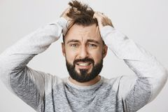 Portrait of depressed bearded guy feeling pressure, grabbing hair with hands and expressing devastation, standing over. Gray background. Huge grief just Stock Photos