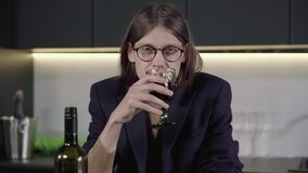 Portrait of depressed brunette man in eyeglasses drinking wine from glass and falling on the table. Young drunk