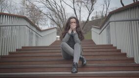 Portrait of depressed Caucasian girl sitting on stairs in city park and crying. Beautiful brunette woman having problems