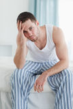 Portrait of a depressed man sitting on his bed Stock Images