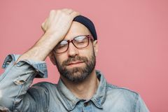 Portrait of depressed middle aged unshaven male closes eyes and keeps hand on forehead, has unhappy expression, isolated over pink. Background. Fatigue hipster stock image