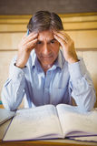 Portrait of depressed professor sitting with notes royalty free stock photography