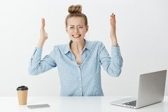 Portrait of depressed upset attractive woman in eyewear, raising palms, clenching teeth and frowning, being under. Pressure at work, sitting in office near Royalty Free Stock Image