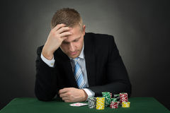 Portrait Of A Depressed Young Male Poker Player. Depressed Male Poker With Chips And Cards On Table Stock Images