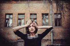 Portrait of depressive emotional girl standing near old building with windows. Vintage tone, sad depression,violence, bipolar conc Royalty Free Stock Photography