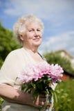 Portrait der älteren lächelnden Frau mit Blumen Lizenzfreie Stockfotografie