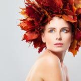 Portrait der attraktiven Nacktheitfrauenbedeckung durch Ahornholzblätter Frau im Kranz von Fall-Blättern Lizenzfreie Stockbilder