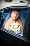Portrait der Braut im Hochzeitsauto Stockbilder