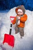 Portrait der entzückenden Schätzchenstütze nahe Schneeschaufel Lizenzfreie Stockfotos