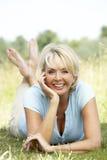 Portrait der fälligen Frau entspannend in der Landschaft lizenzfreies stockfoto