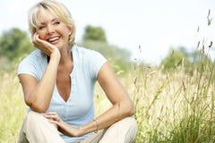 Portrait der fälligen Frau sitzend in der Landschaft