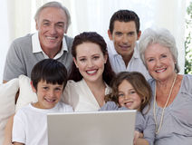 Portrait der Familie sitzend auf Sofa unter Verwendung eines Laptops Stockbild