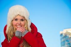 Portrait der Frau im roten Mantelblau backgound Lizenzfreie Stockfotos