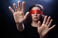 Portrait der Frau mit rotem Verband auf Augen Stockfotografie