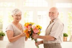 Portrait der glücklichen älteren Paare mit Blume Stockfotografie