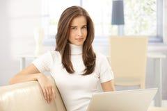 Portrait der hübschen Frau auf Sofa lizenzfreie stockbilder