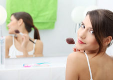 Portrait der jungen erwachsenen Frau, die Blusher anwendet stockbilder