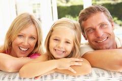 Portrait der jungen Familie zusammen entspannend auf Sofa lizenzfreies stockfoto
