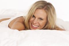 Portrait der jungen Frau im Bett stockbild