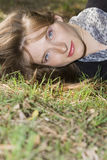 Portrait der jungen Frau liegend auf dem Gras Stockbilder