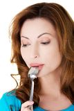 Portrait der jungen Frau mit Löffel in ihrem Mund Stockbild