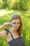 Portrait der jungen Frau mit Lupe Stockbild