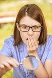 Portrait der jungen Frau mit Lupe Stockfotos
