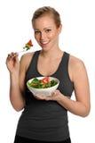 Portrait der jungen glücklichen Frau, die Salat isst Lizenzfreies Stockfoto