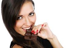 Portrait der jungen lächelnden Frau, die Schokolade isst Stockbilder