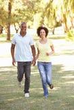 Portrait der jungen Paare, die durch Park laufen Stockfoto