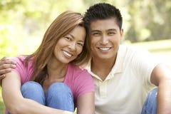 Portrait der jungen Paare, die im Park sitzen stockfotografie