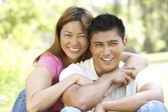 Portrait der jungen Paare, die im Park sitzen stockbilder