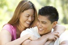 Portrait der jungen Paare, die im Park sitzen lizenzfreie stockbilder
