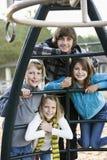 Portrait der Kinder auf Spielplatzausrüstung Stockbild