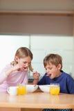 Portrait der Kinder, die frühstücken Stockbild