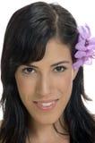 Portrait der lächelnden Frau mit Blume in ihrem Haar Stockfotografie