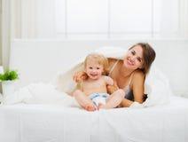 Portrait der lächelnden Mutter und des Schätzchens im Schlafzimmer Stockfoto