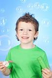 Portrait der lustigen durchbrennenseifenluftblasen des kleinen Jungen Lizenzfreie Stockbilder
