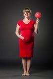 Portrait der lustigen schwangeren Frau im roten Kleid lizenzfreies stockfoto