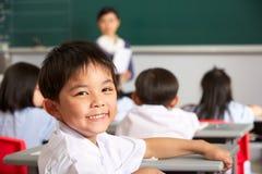 Portrait der männlichen Pupille am Schreibtisch in der chinesischen Schule Stockbilder