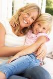 Portrait der Mutter und der Tochter, die auf Sofa sich entspannen Lizenzfreies Stockbild